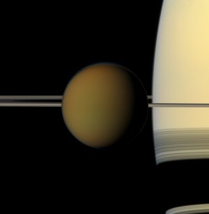 Saturn's largest moon, Titan, passes in front of the planet and its rings in this true color snapshot from NASA's Cassini spacecraft. This view looks toward the northern, sunlit side of the rings from just above the ring plane. It was taken on May 21, 2011, when Cassini was about 1.4 million miles (2.3 million kilometers) from Titan.